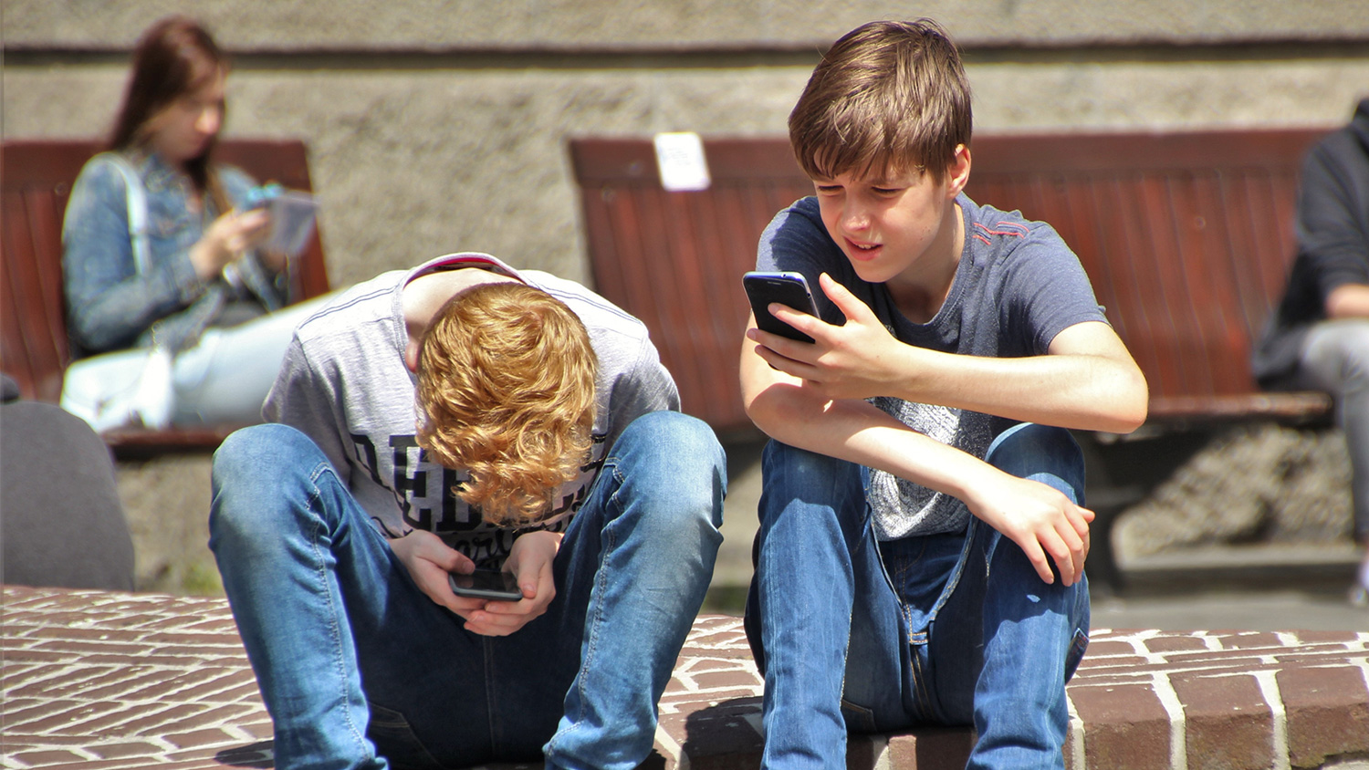 2 young kids on there phones