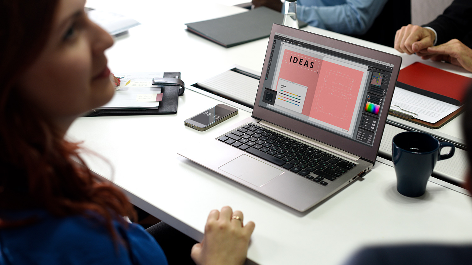 people at meeting with laptop open on table